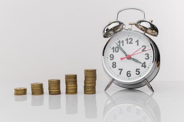 기회 비용 시간의 개념. 돈 시계와 나무 테이블에 동전