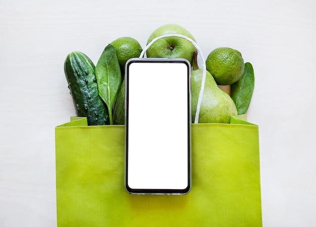 Концепция заказа свежих овощей и фруктов. зеленый огурец, лайм, шпинат, яблоко в крафтовой сумке.