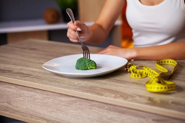 Концепция полных женщина ест диету брокколи