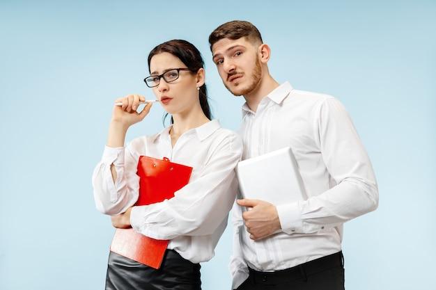 비즈니스 파트너십의 개념. 스튜디오에서 파란색 배경에 젊은 감정적 인 남자와 여자. 인간의 감정과 파트너십 개념