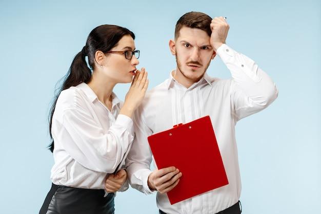 ビジネスにおけるパートナーシップの概念。青い背景の若い感情的な男と女