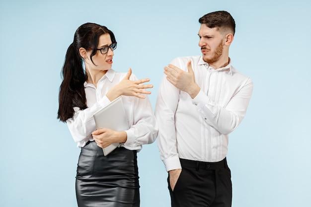 비즈니스 파트너십의 개념. 파란색 벽에 젊은 감정적 인 남자와 여자. 인간의 감정과 파트너십 개념
