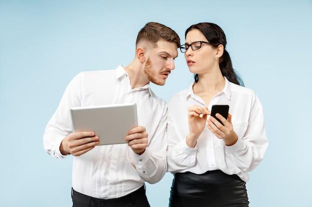 ビジネスにおけるパートナーシップの概念。青い壁に対して若い感情的な男と女。人間の感情とパートナーシップの概念