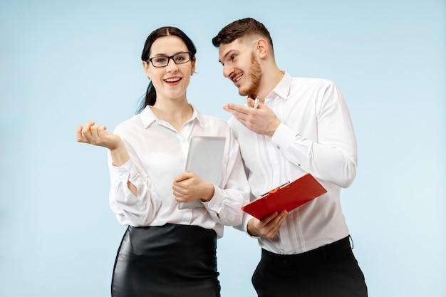 ビジネスにおけるパートナーシップの概念。スタジオで青い背景に立っている若い幸せな笑顔の男と女