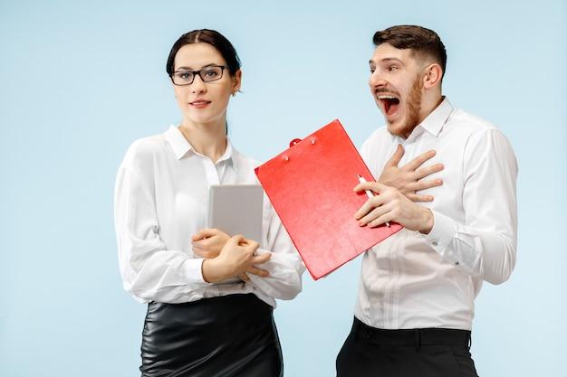 ビジネスにおけるパートナーシップの概念。青い背景に立っている若い幸せな笑顔の男と女
