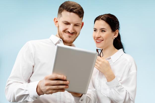 Концепция партнерства в бизнесе. молодой счастливый улыбающийся мужчина и женщина, стоящие у синей стены
