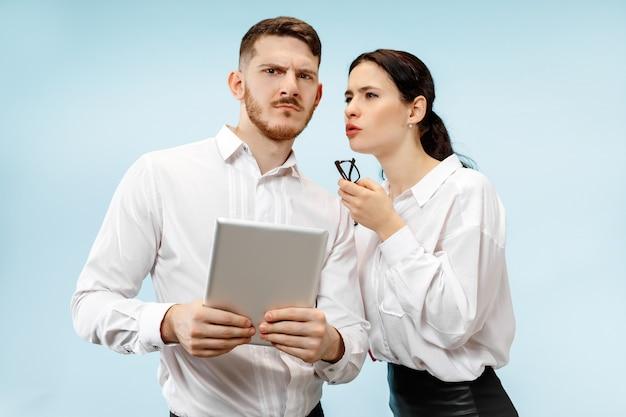 ビジネスにおけるパートナーシップの概念。スタジオで青い背景に対して疑わしい若い男と女