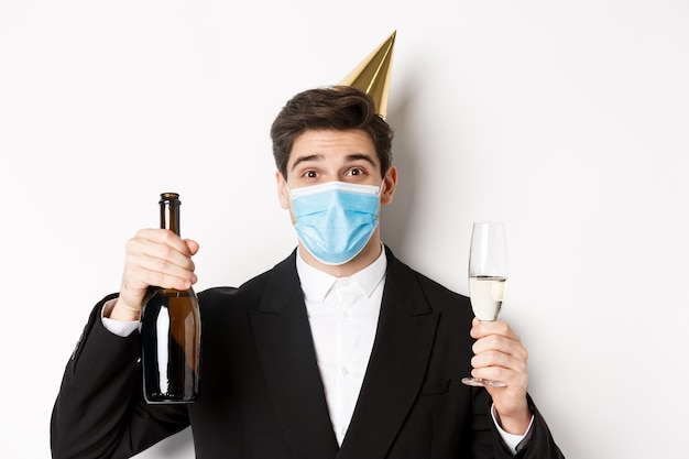 Covid-19 동안 파티의 개념입니다. 양복을 입은 잘생긴 남자, 재미있는 모자, 의료용 마스크, 샴페인 한 병을 들고 코로나바이러스 기간 동안 새해를 축하하는 클로즈업