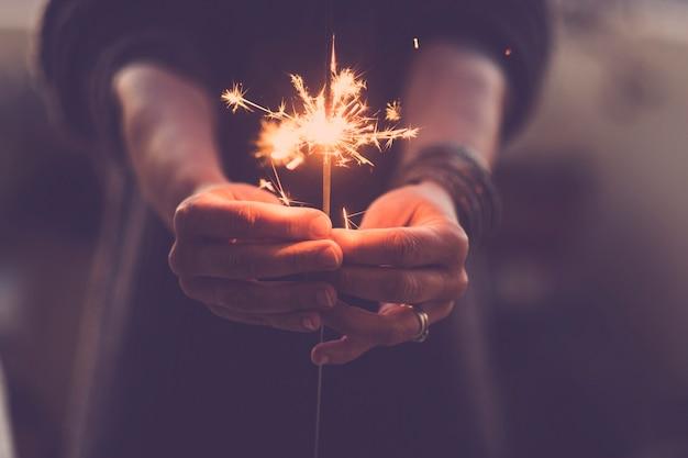 パーティーのナイトライフと2020年の大晦日のコンセプト-夜と新しいスタートを祝うために赤い線香花火で人々の手をクローズアップ-暖かい色のフィルター