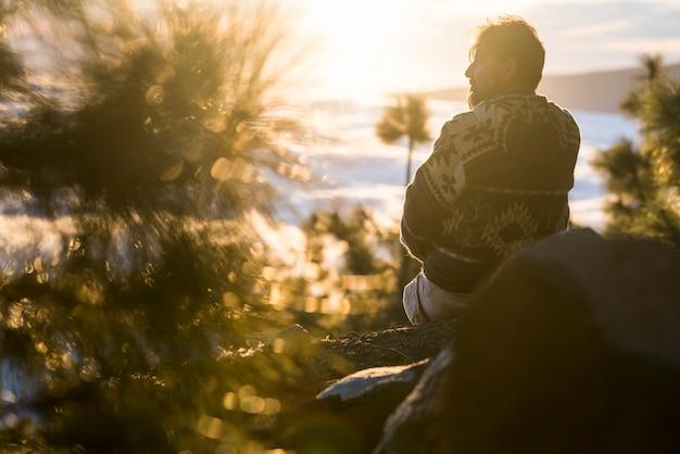 人と屋外の自然のライフスタイルの概念-岩の上に座って、背景の美しい夕日と風景を楽しむ男-山岳観光休日休暇ライフスタイル