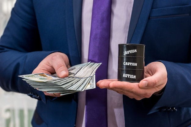 Понятие цены на нефть - мужчина держит доллар и баррель