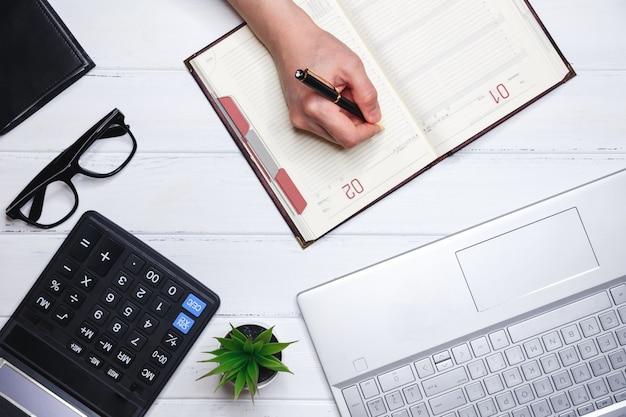 Концепция планирования и успешного ведения бизнеса. человеческая рука записывает в дневник планы текущих дел, обучения, реализации и развития бизнеса.