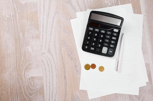 Концепция планирования бюджета, бизнеса, финансового планирования, экономии денег, налогов или концепции бухгалтерского учета, банкротства, вид сверху или плоские деньги, расчет, список и ручка на сером фоне.