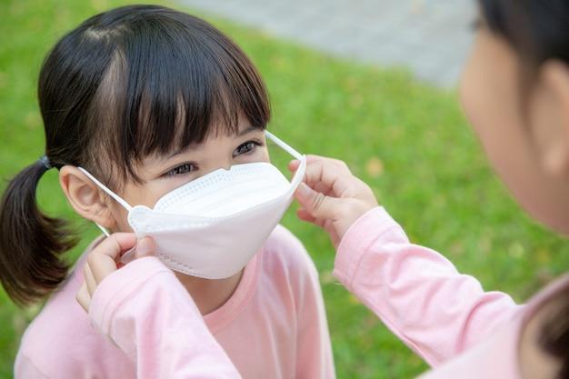 コロナウイルスcovid-19とウイルス感染を防ぐための概念。母親は学校に行く前に小さな女の子のために医療用マスクを着用します