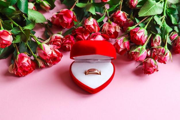 제안, 결혼식 및 사랑의 개념. 꽃으로 둘러싸인 선물 상자에 금 결혼 반지