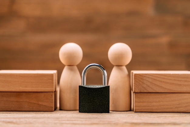 保護と支援の概念。木製の置物は南京錠で立っています