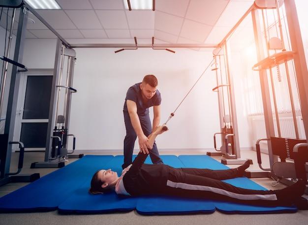 재활의 개념. 물리 치료사의 감독하에 매트에 운동을하는 아름 다운 젊은 여자