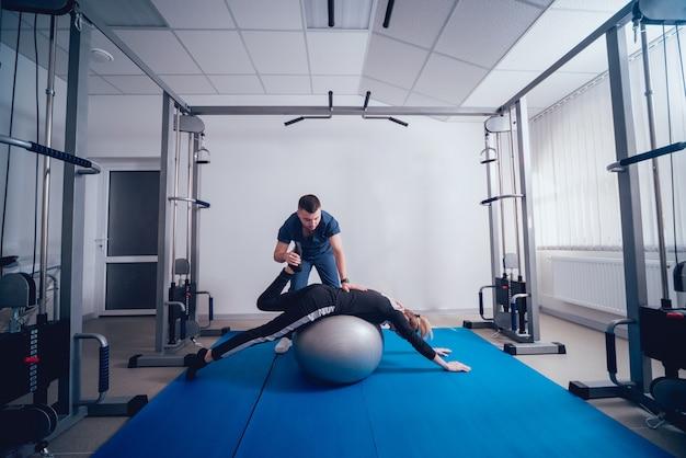 재활의 개념. 물리 치료사의 감독하에 공 운동을하는 아름 다운 젊은 여자
