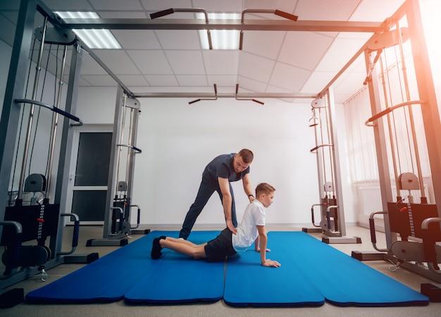 재활의 개념. 물리 치료사의 감독하에 매트에 운동을하는 어린 소년