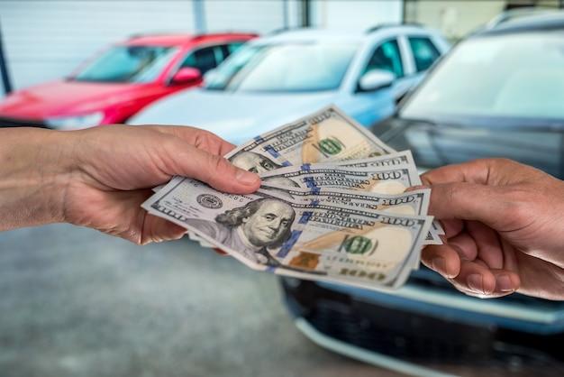 임대 또는 새 차 구입의 개념. 금융 개념. 남성 달러 달러