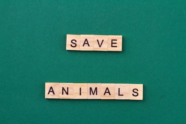 ペットを救助するという概念。フレーズ保存動物とアルファベットの木製ブロック。緑の背景に分離。