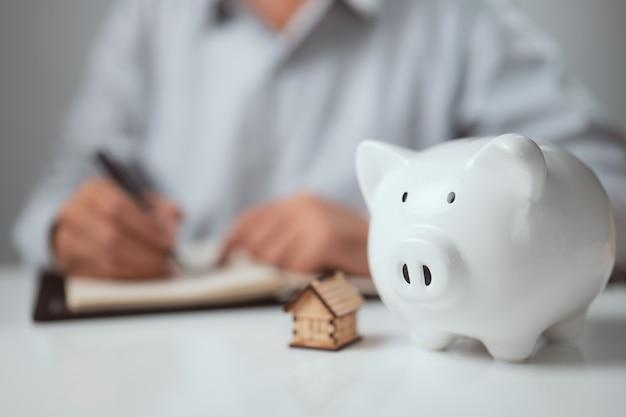 財政をしている人と貯金箱を保存し、ホームオフィスの机の上で計算するという概念