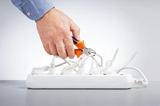 エネルギー節約の概念。エネルギーを節約するために電線を切断するワイヤーカッターを備えた男性の手。