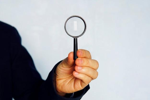 検索の概念。青い背景に拡大鏡を保持している青いスーツのビジネスマンのクローズアップ