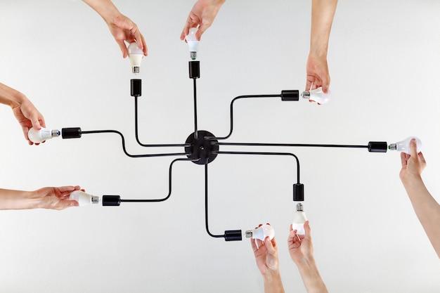 천장 조명에서 led 램프를 교체 할 때 팀워크 중 단결 된 행동의 예에 대한 공유 가치 또는 공유 목적의 개념.