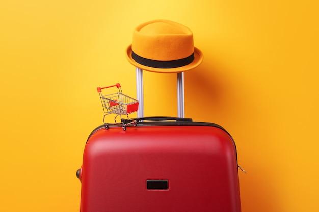 Концепция покупок за границей, шляпа в чемодане с корзиной на желтом фоне