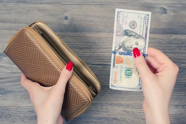쇼핑의 개념입니다. 지갑에서 돈을 꺼내는 여성의 손 사진을 클로즈업