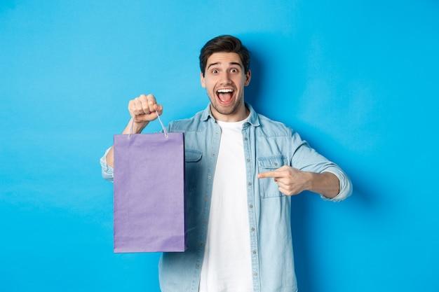 ショッピング、休日、ライフスタイルの概念。興奮した男が紙袋に指を向けて驚いたように見え、店を推薦し、割引を発表し、青い背景