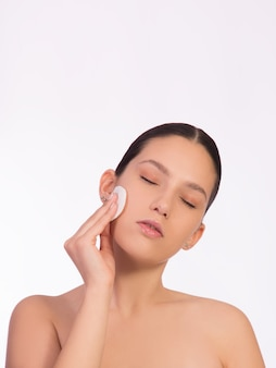 피부 청소의 개념, 메이크업 제거, 깨끗한 건강한 피부. 젊은 여자는 그녀의 얼굴에 화장품 패드를 들고.