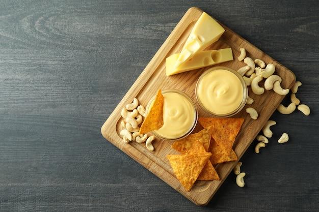 暗い木製のテーブル、上面図にチーズソースとスナックの概念