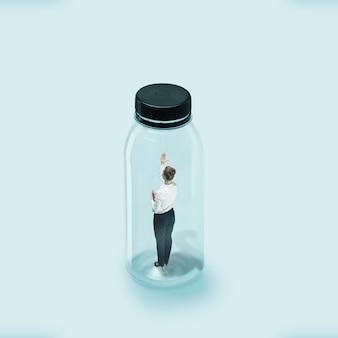 コロナウイルスの世界的大流行時の社会的距離の概念、仕事と日常の安全。若い女性労働者は、ウイルスが侵入しないようにガラス瓶に閉じこめられました。ヘルスケア、医学、アートワーク。