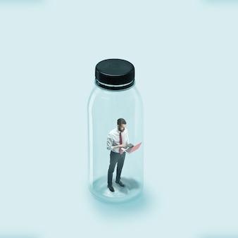 コロナウイルスの世界的大流行時の社会的距離の概念、仕事と日常の安全。若い男性労働者は、ウイルスが侵入しないようにガラス瓶に閉じこめられました。ヘルスケア、医学、アートワーク。