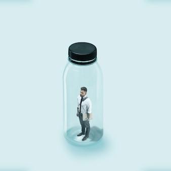 コロナウイルスの世界的大流行時の社会的距離の概念、仕事と日常の安全。若いサラリーマンがガラス瓶に閉じこもり、ウイルスが侵入しないようにしました。ヘルスケア、医療、アートワーク。