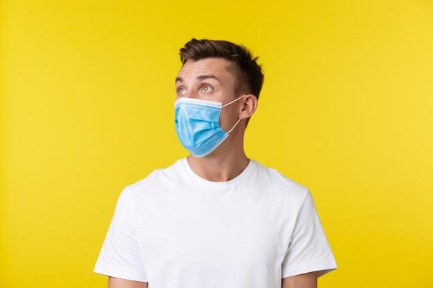 社会的距離、covid-19および人々の感情の概念。医療マスクで驚いてショックを受けた金髪の男のクローズアップの肖像画、眉を上げ、言葉のない黄色の背景を見つめています。