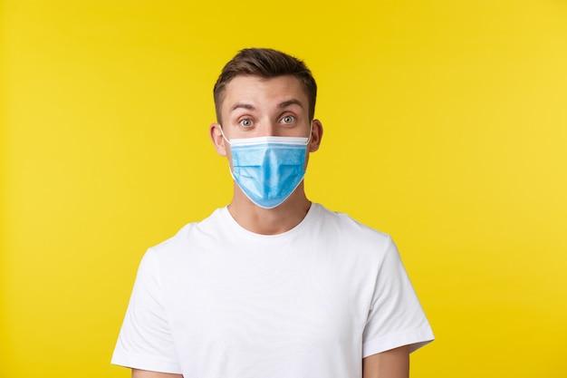 사회적 거리, covid-19 및 사람들의 감정의 개념. 흥분하고 놀란 잘생긴 남자는 의료용 마스크를 쓰고 노란색 배경 위에 놀란 표정을 하고 놀라운 소식을 발견했습니다.