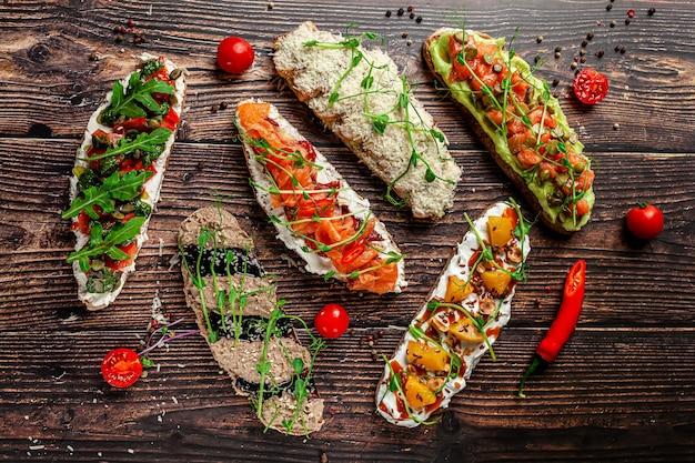 스페인 요리의 개념. 튀긴 바게트에 타파스 다른 브루스케타. 레스토랑에서 요리를 제공합니다. 배경 이미지. 공간을 복사하십시오.