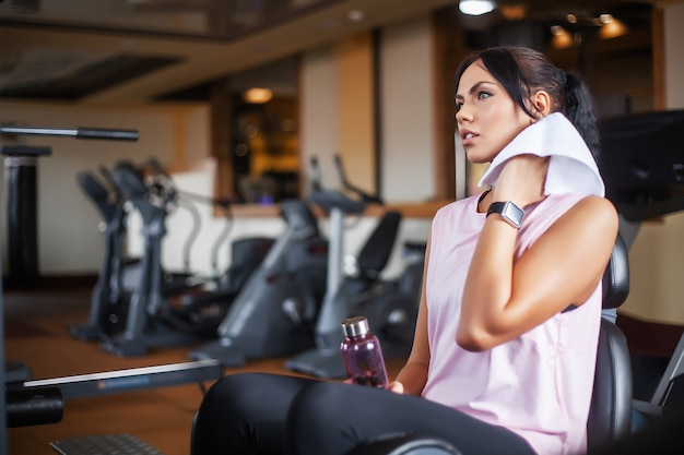スポーツと健康的なライフスタイルのコンセプトです。白いスポーツウェアを着ているトレッドミルで実行されている若い魅力的なフィットネス女性。トレッドミルで有酸素運動を行う健康なスポーティな女性