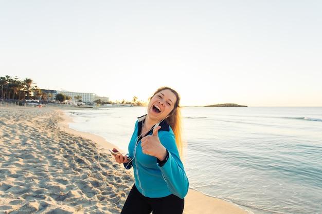 스포츠, 피트니스, 건강한 생활 방식, 달리기의 개념 - 해변에서 야외 운동을 한 후 엄지손가락을 치켜드는 운동을 하는 스포티한 여성.