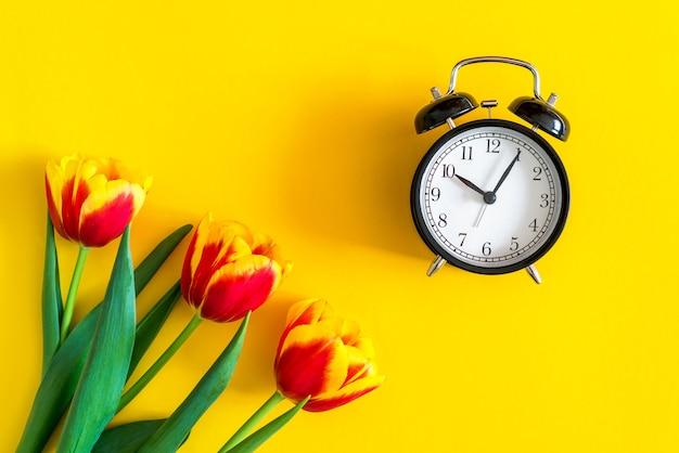 春の時間の概念。時計の近くの黄色の背景に赤いチューリップ。新鮮なフラットレイ