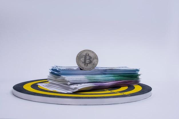 Понятие успеха и достижения цели. круглая доска для дартса с пачкой долларов, евро и биткойн-монетой в центре круга.