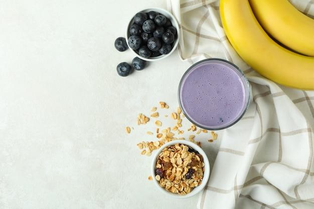 Концепция вкусного завтрака с черничным смузи на белом текстурированном столе