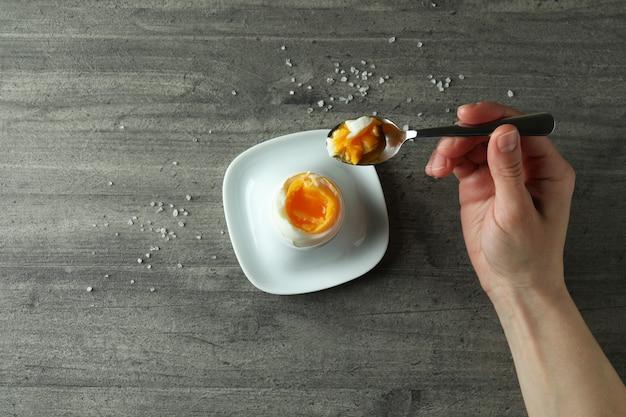 灰色のテクスチャ背景にゆで卵とおいしい朝食の概念