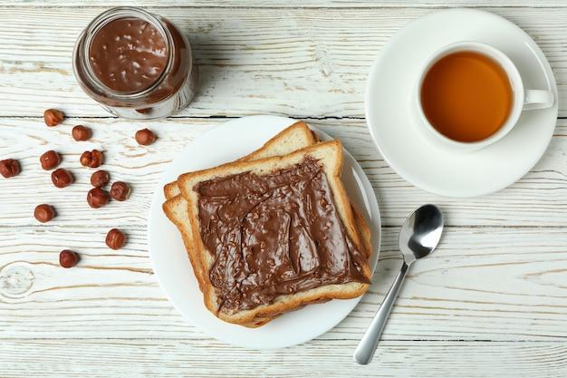 Концепция вкусного завтрака с шоколадной пастой на белом деревянном столе