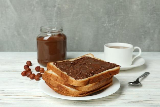 흰색 나무 테이블에 초콜릿 페이스트를 넣은 맛있는 아침 식사의 개념