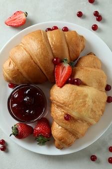 Концепция вкусного завтрака с круассанами на белом текстурированном столе