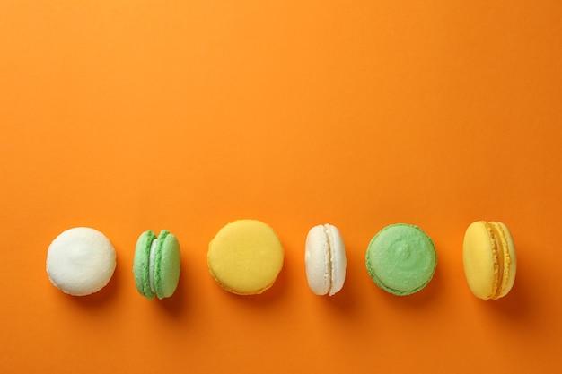 Концепция вкусного десерта с макаронами на оранжевом фоне
